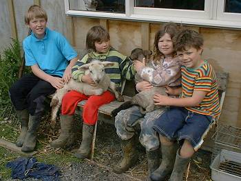 Neil, Lenita, Kendra and Sebastian holding two of the lambs