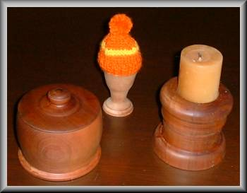 turned wood: a lidded round box, a candle stick and an egg-cup (with a silly hat on)